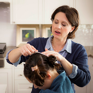 mom performing at home lice removal treatment